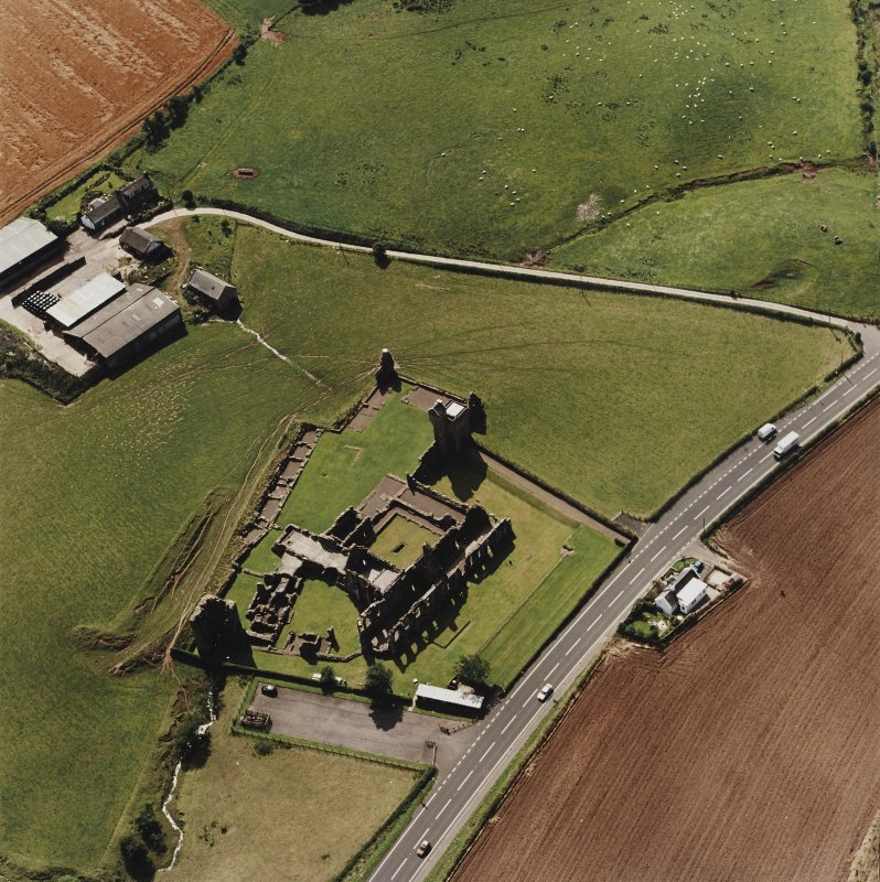 Oblique aerial view centred on the remains of the abbey and the doocot and cottage, taken from the NE.
