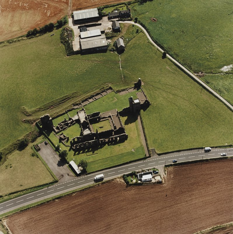 Oblique aerial view centred on the remains of the abbey and the doocot and cottage, taken from the N.