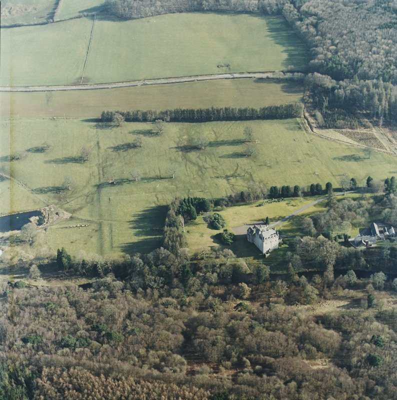 Oblique aerial view centred on the tower-house with the stables adjacent, taken from the NW.
