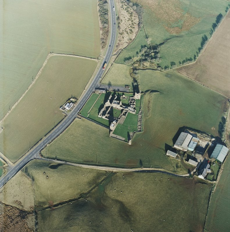 Oblique aerial view centred on the remains of the abbey with the farmsteading and cottage adjacent, taken from the SW.
