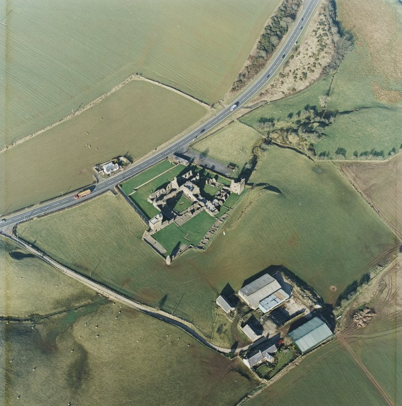 Oblique aerial view centred on the remains of the abbey with the farmsteading and cottage adjacent, taken from the SSW.