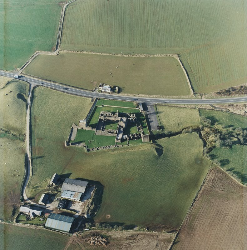 Oblique aerial view centred on the remains of the abbey with the farmsteading and cottage adjacent, taken from the S.