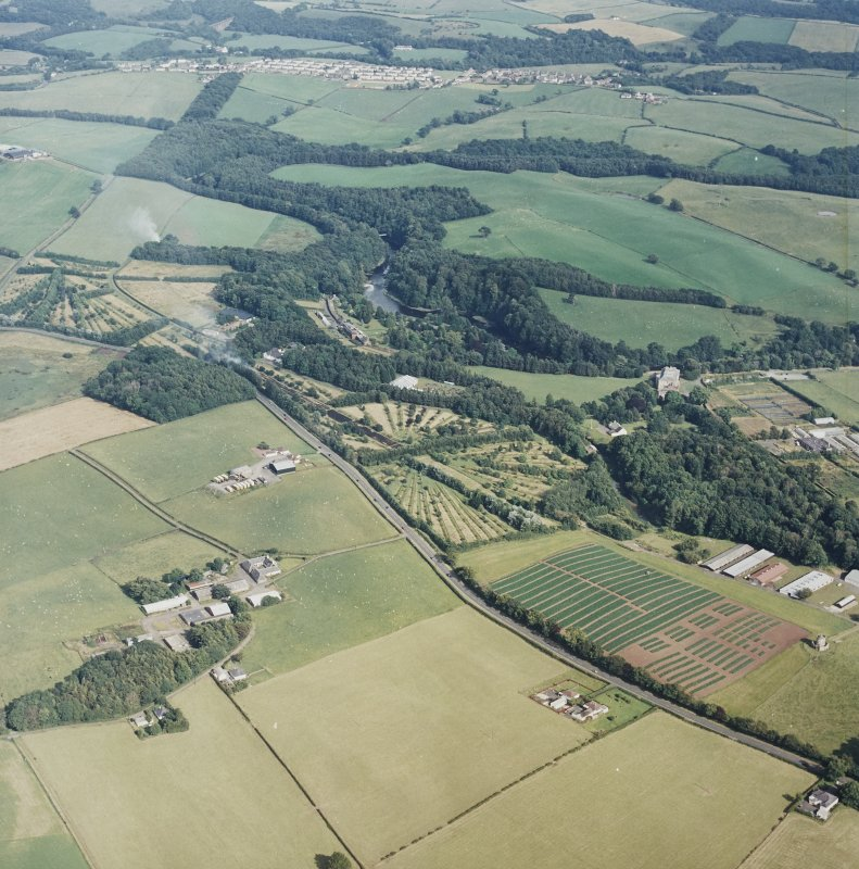General oblique aerial view looking across the tower-house, school and agricultural college towards the village, taken from the NW.