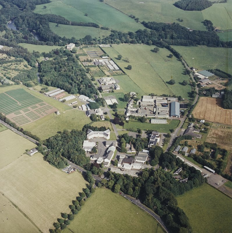 Oblique aerial view centred on the school and agricultural college with the tower-house adjacent, taken from the NW.