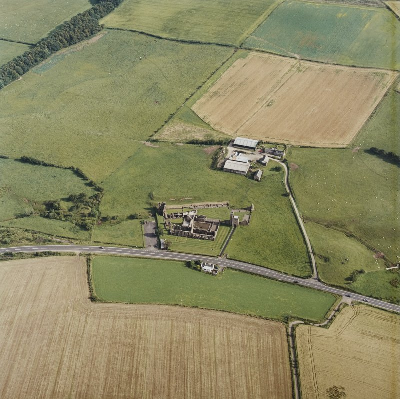 Oblique aerial view centred on the farmsteading and the remains of the abbey, taken from the NNW.