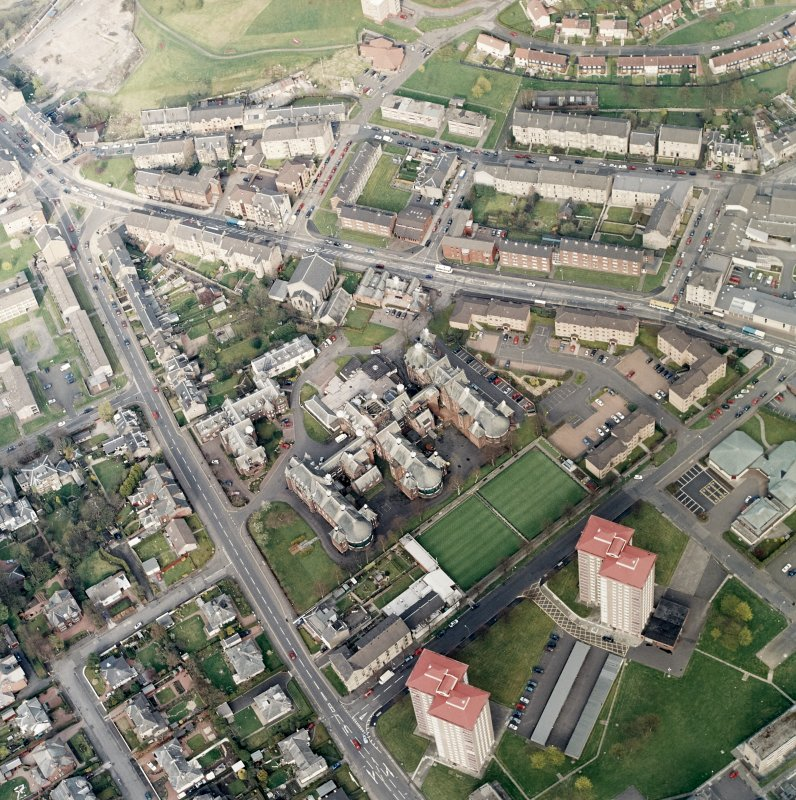 Oblique aerial view centred on the hospital and churches, taken from the SW.