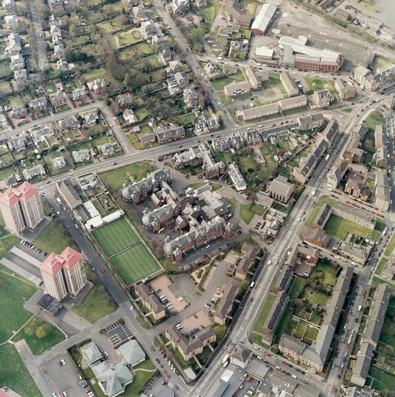 Oblique aerial view centred on the hospital and churches, taken from the SE.