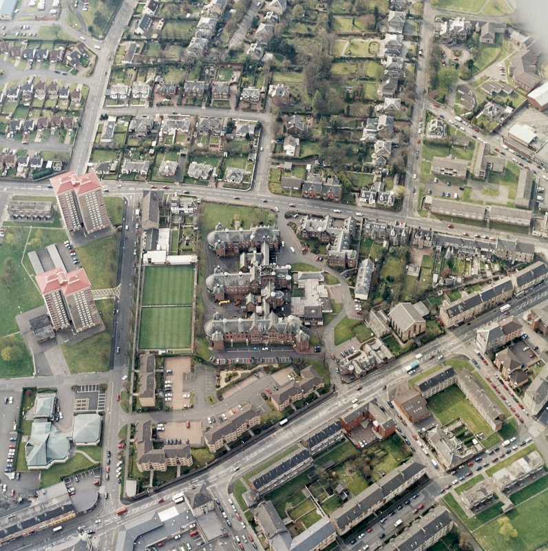 Oblique aerial view centred on the hospital and churches, taken from the ESE.