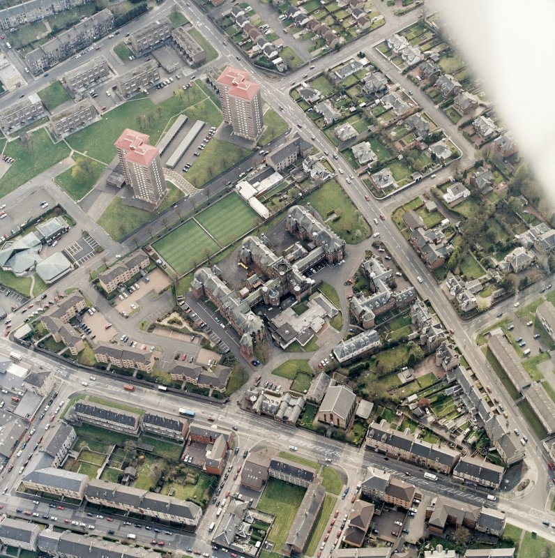 Oblique aerial view centred on the hospital and churches, taken from the ENE.