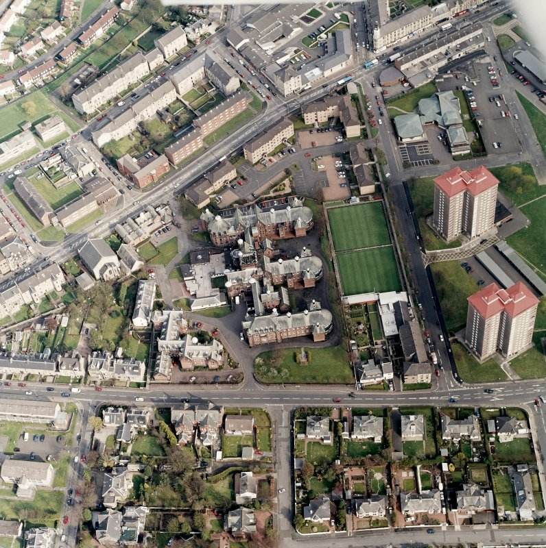 Oblique aerial view centred on the hospital and churches, taken from the NW.