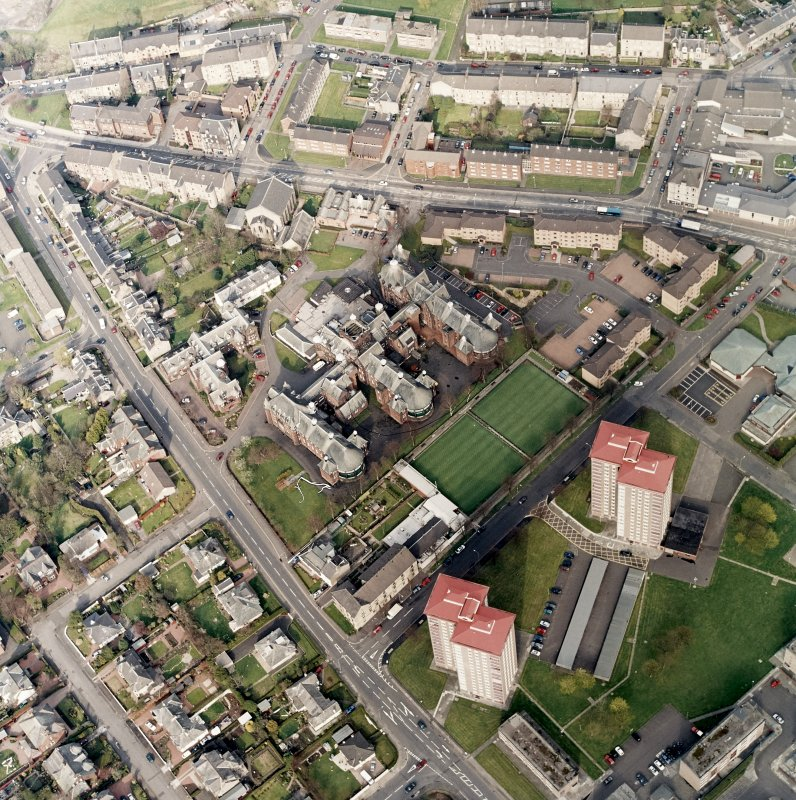 Oblique aerial view centred on the hospital and churches, taken from the WSW.