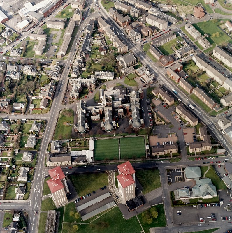 Oblique aerial view centred on the hospital and churches, taken from the SSW.