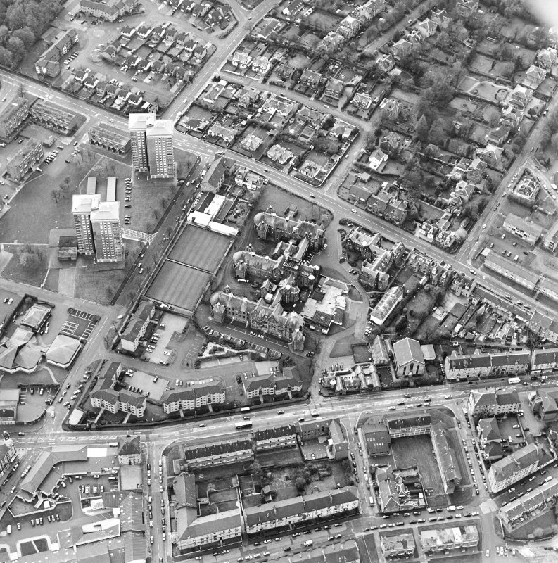 Oblique aerial view centred on the hospital and churches, taken from the E.