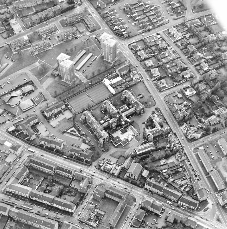 Oblique aerial view centred on the hospital and churches, taken from the NE.