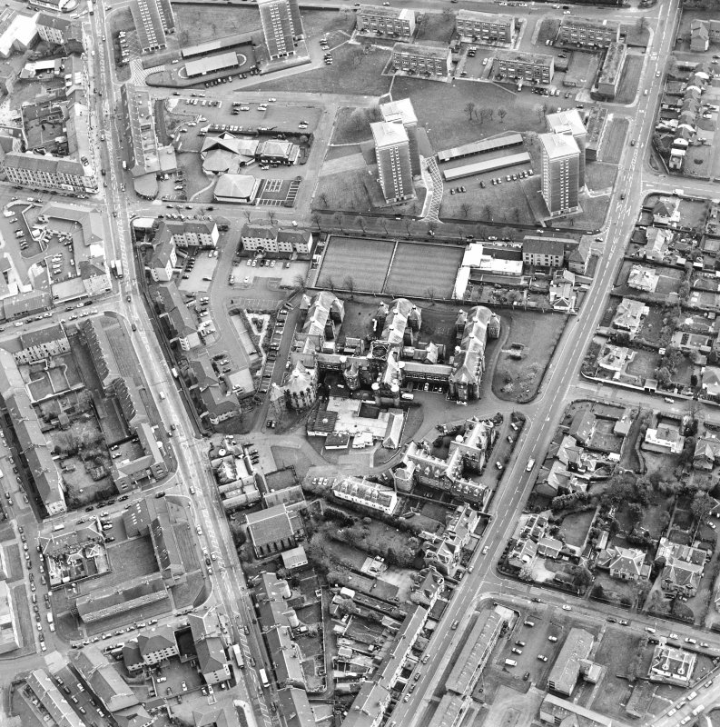 Oblique aerial view centred on the hospital and churches, taken from the N.