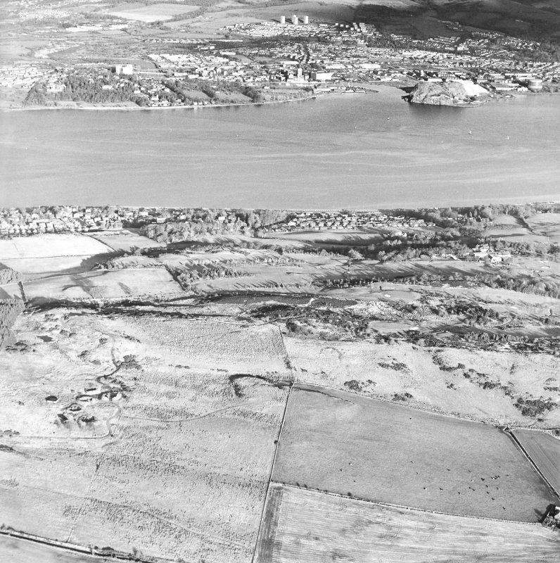 General oblique aerial view looking across the remains of an anti-aircraft battery towards Dumbarton Rock, taken from the SSW.