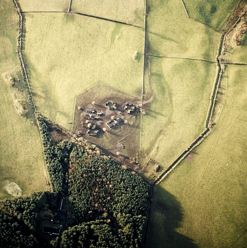Oblique aerial view centred on the remains of the four gun-emplacements and command and control building with the remains of the accommodation camp in the small plantation, taken from the E.