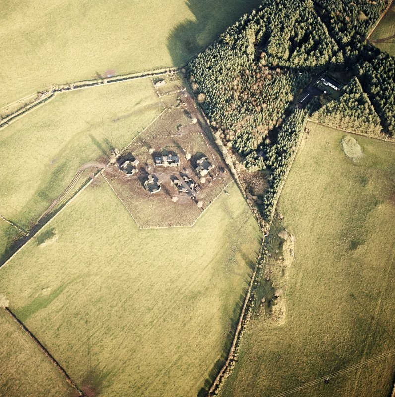 Oblique aerial view centred on the remains of the four gun-emplacements and command and control building with the remains of the accommodation camp in the small plantation, taken from the SW.