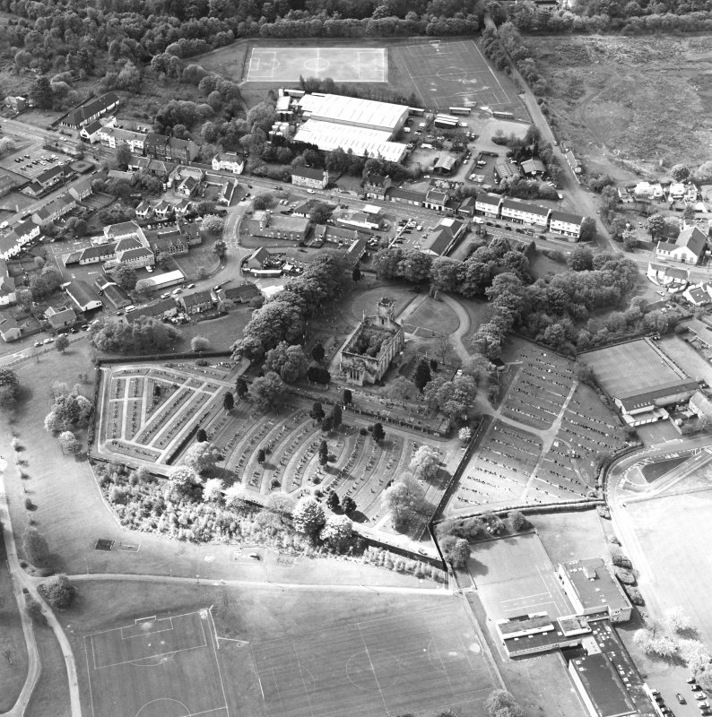 Oblique aerial view of Lennoxtown centred on the remains of the church and cemetery, taken from the NE.