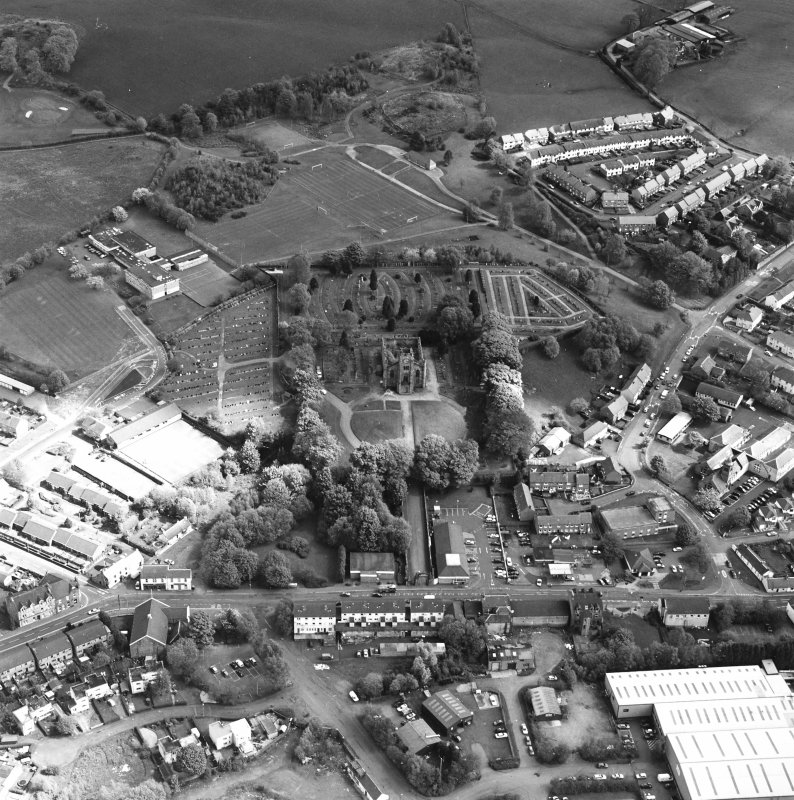 Oblique aerial view of Lennoxtown centred on the remains of the church and cemetery, taken from the SW.