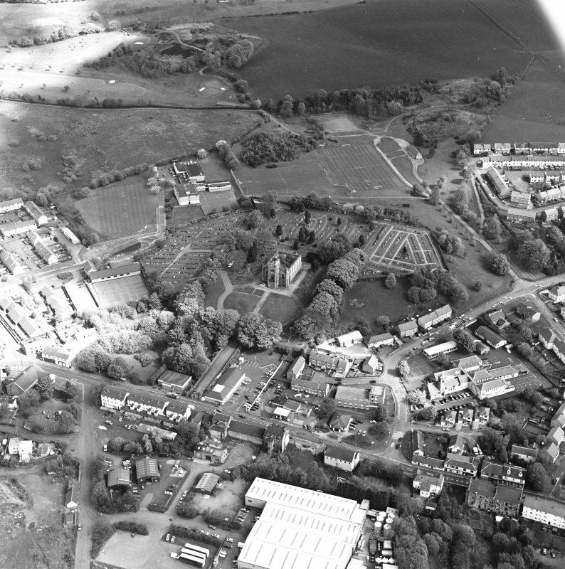 Oblique aerial view of Lennoxtown centred on the remains of the church and cemetery, taken from the SSW.