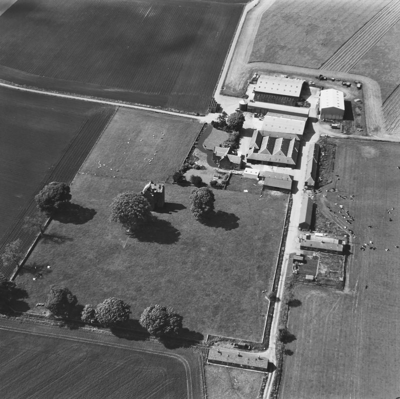 Oblique aerial view from SE with farm buildings.