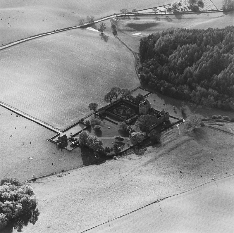 Oblique aerial view of Edzell Castle centred on the remains of the castle with motte-and-bailey castle, church and burial ground adjacent, taken from the NE.