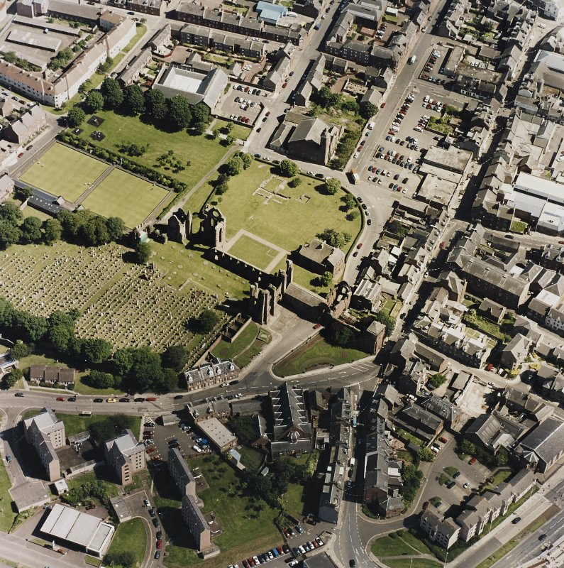Oblique aerial view centred on the remains of the abbey and churchyard, taken from the NW.