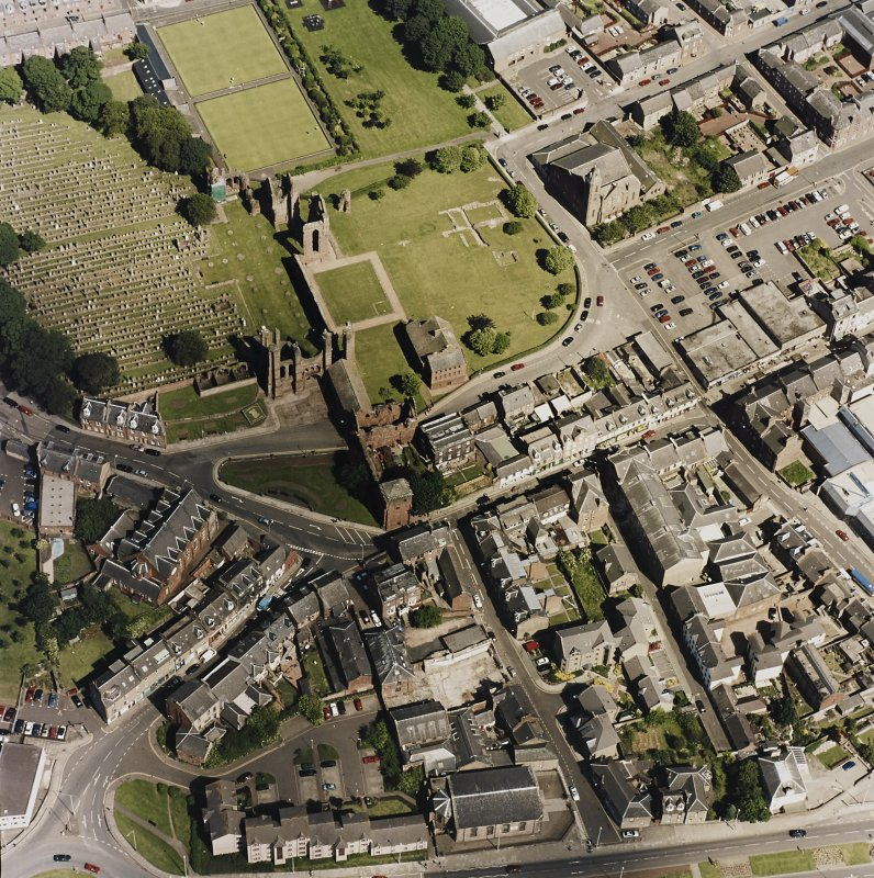 Oblique aerial view centred on the remains of the abbey and churchyard, taken from the W.