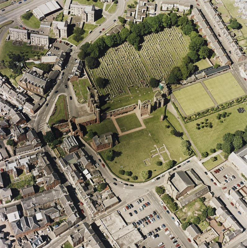 Oblique aerial view centred on the remains of the abbey and churchyard, taken from the S.