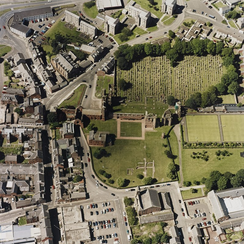 Oblique aerial view centred on the remains of the abbey and churchyard, taken from the SSE.