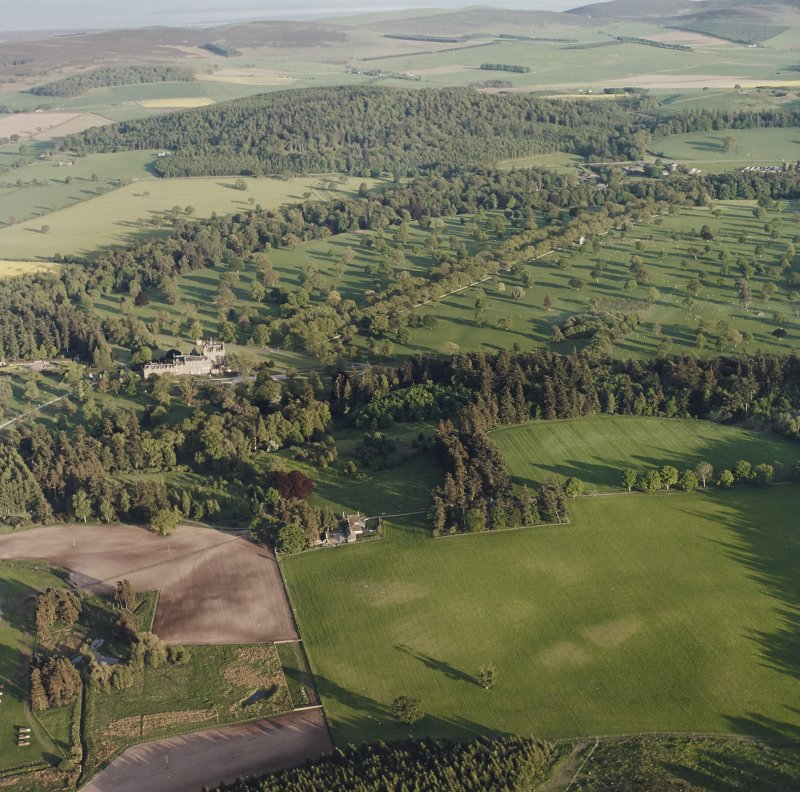 Glamis Castle and Muir House, oblique aerial view, taken from the NNW, centred on Glamis Castle and Gardens. Cropmarks of rig are visible in the foreground.