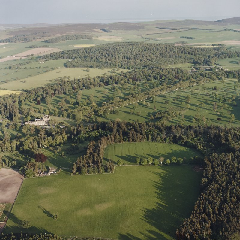 Glamis Castle and Muir House, oblique aerial view, taken from the NW, centred on Glamis Castle and Gardens. Cropmarks of rig are visible in the foreground.