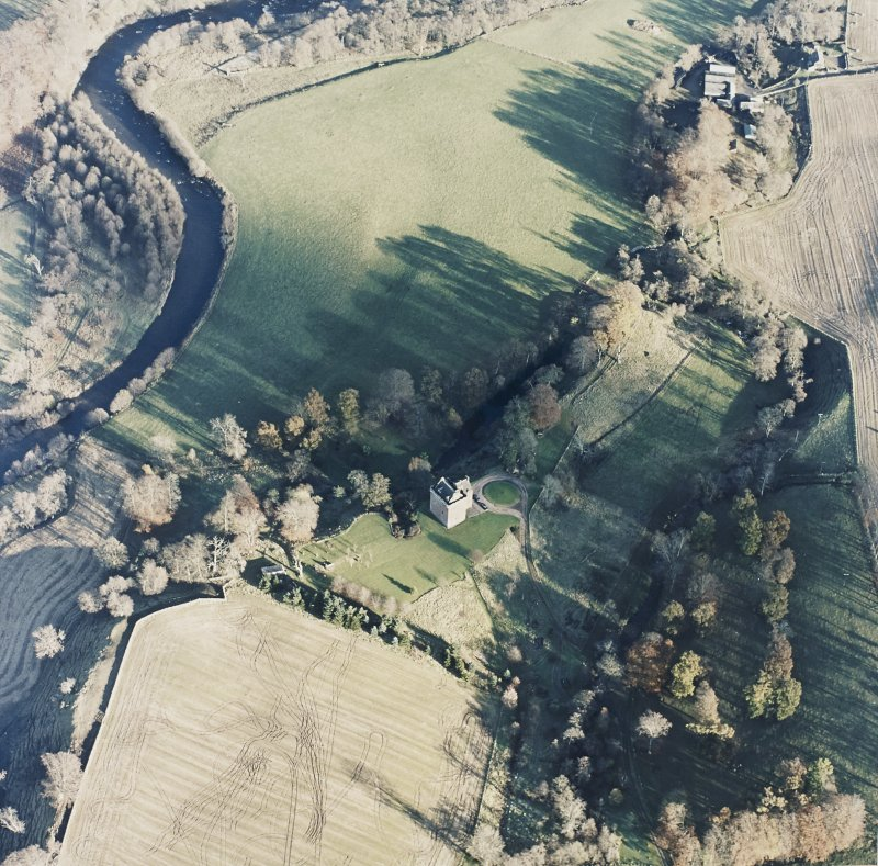 Oblique aerial view centred on the tower-house with watermill adjacent, taken from the WSW.