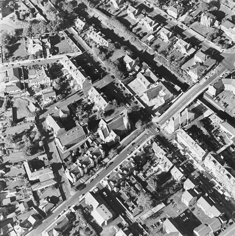 Oblique aerial view centred on the churches and church hall, taken from the SE.