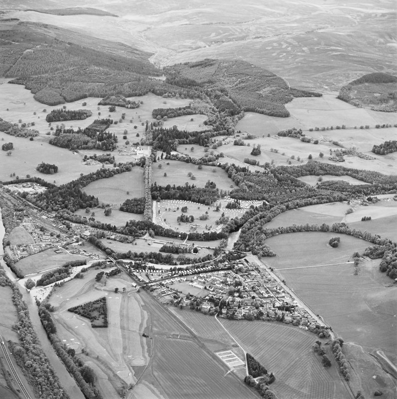 Oblique aerial view of Blair Castle centred on the country house, with Blair Atholl village and a road bridge adjacent, taken from the SE.