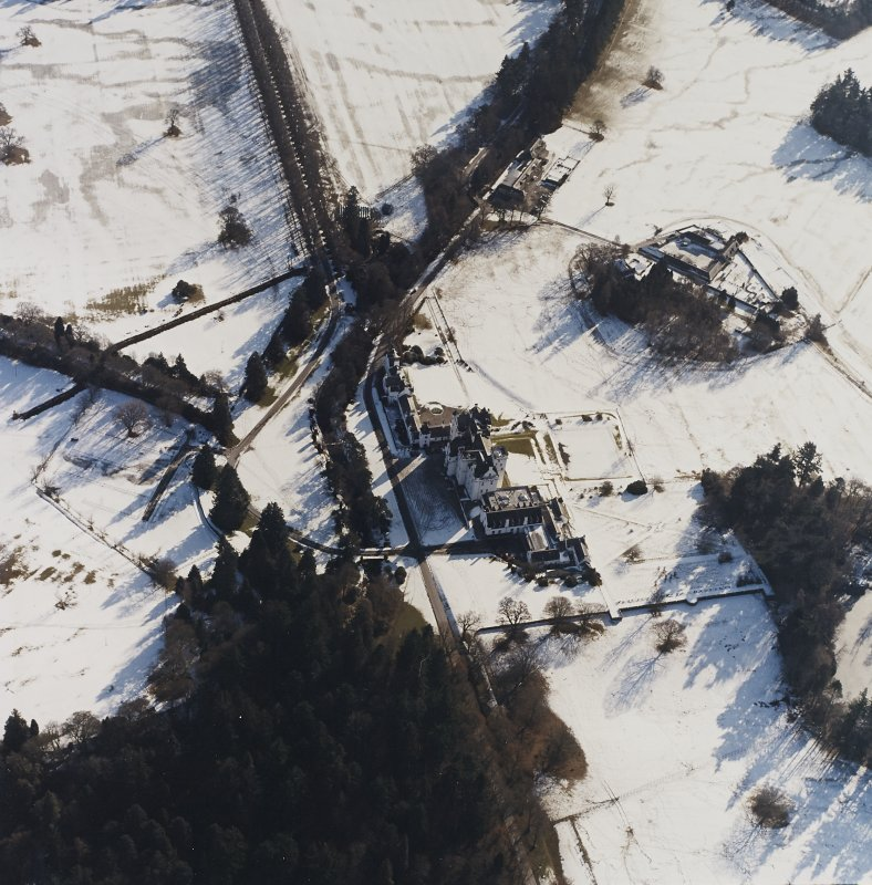 Oblique aerial view centred on the country house and garden, with the dairy and estate offices adjacent, taken from the NNW.