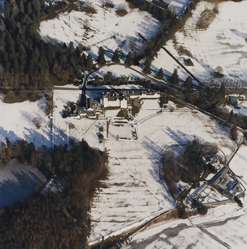Oblique aerial view centred on the country house and garden, with the dairy adjacent, taken from the SW.
