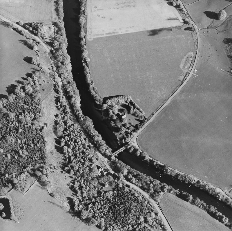 Oblique aerial view centred on the remains of the tower-house with road bridge adjacent, taken from the NW.