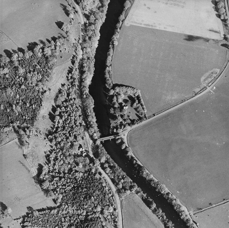 Oblique aerial view centred on the remains of the tower-house with road bridge adjacent, taken from the WNW.