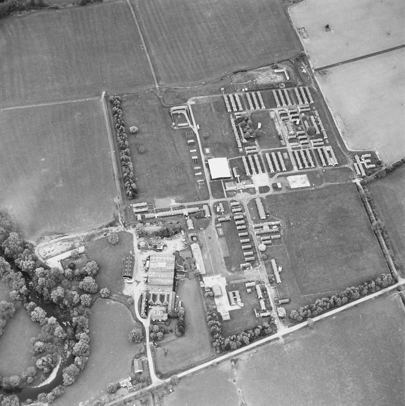 Oblique aerial view centred on the military camp with the bunker, observation post and remains of the church and graveyard adjacent, taken from the SSE.