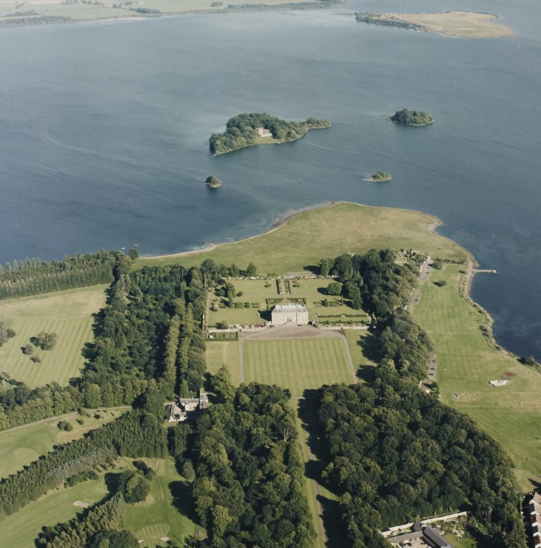 Oblique aerial view of Kinross House centred on the country house with garden and stables, and with a church, burial ground and castle in the background, taken from the WNW.