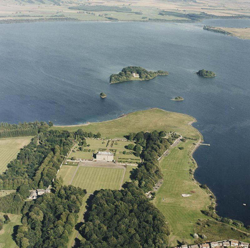 Oblique aerial view of Kinross House centred on the country house with garden and stables, and with a church, burial ground and castle in the background, taken from the W.