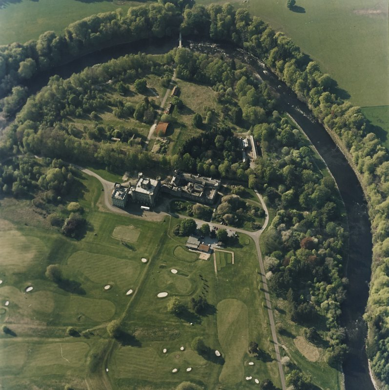 Oblique aerial view centred on the country house with golf club house and remains of military camp adjacent, taken from the SE.