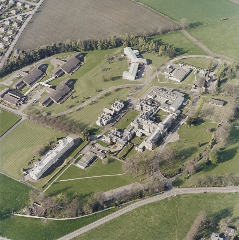 Oblique aerial view centred on the hospital and chapel, taken from the SW.