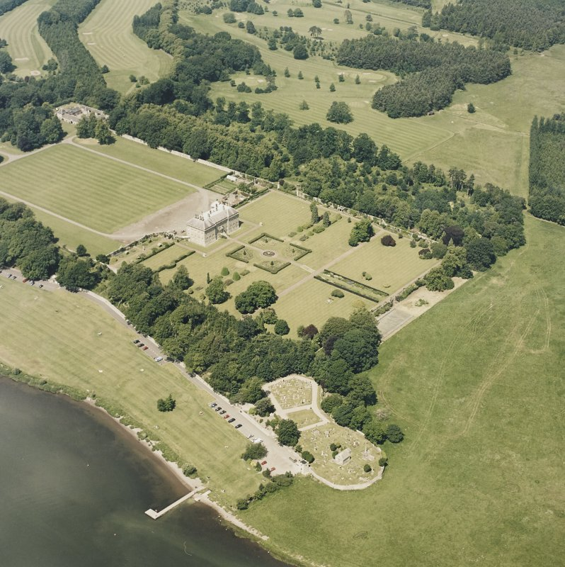 Oblique aerial view of Kinross House centred on the country house, garden, stables, and church and burial ground in the foreground, taken from the S.