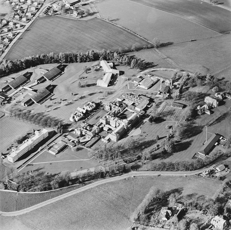 Oblique aerial view centred on the hospital and chapel with the remains of the rig adjacent, taken from the SW.