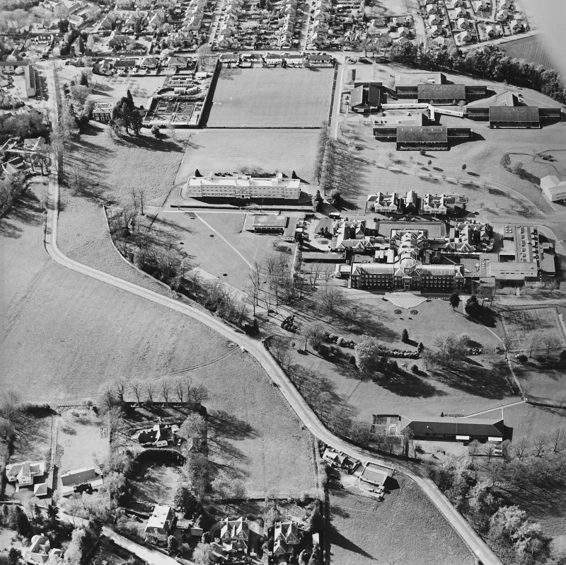 Oblique aerial view centred on the hospital and chapel with the remains of the rig adjacent, taken from the SE.