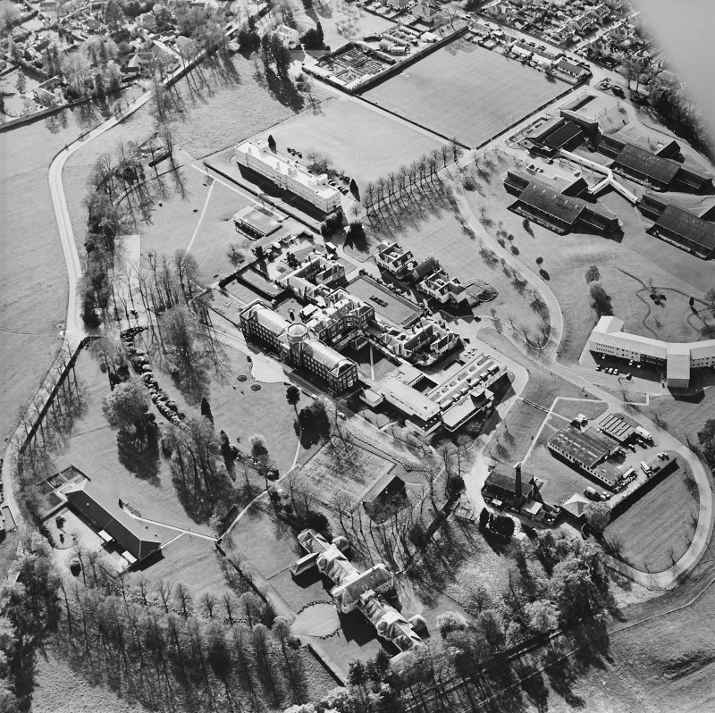 Oblique aerial view centred on the hospital and chapel, taken from the ESE.