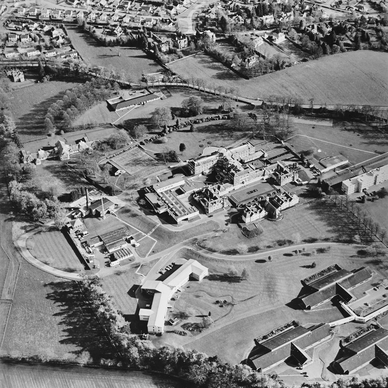 Oblique aerial view centred on the hospital and chapel with the remains of the rig adjacent, taken from the N.
